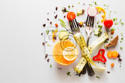 Naklejka vegetables on forks with measuring tape on a white background with place for text. concept diet, weight loss, fat loss