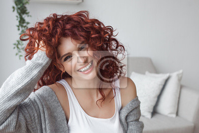 Naklejka Very attractive young woman close up portrait. Beautiful female indoor. Curly haired lady. Red-haired girl. Redhead with wavy hair.