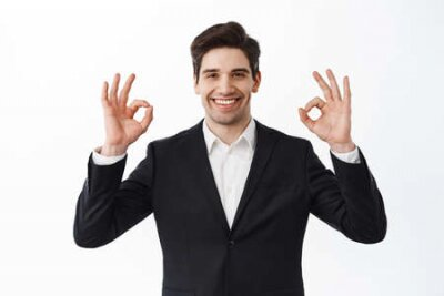 Naklejka Very good. Smiling satisfied businessman, male entrepreneur in business suit, show okay signs and nod in approval, say yes, agree and praise work, white background