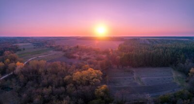 View from above of the countryside in the evening. Pink sky at sunset