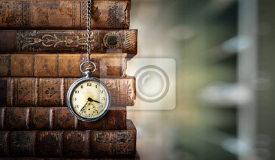 Naklejka Vintage clock hanging on a chain on the background of old books. Old watch as a symbol of passing time. Concept on the theme of history, nostalgia, old age. Retro style.