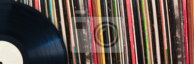 Naklejka Vinyl record in front of a collection of albums, vintage music concept