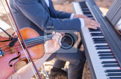 Naklejka Violin and piano musical duo performing during outdoor party
