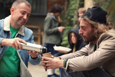 Naklejka Volunteer giving drink to homeless man outdoors
