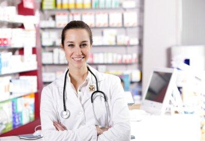 W aptece. Uśmiecha się młoda kobieta z Stetoskop farmaceuta