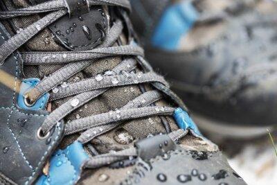 Naklejka waterproof hiking boots. closeup of footwear with rain water drops
