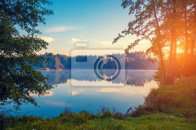 Wczesny poranek, wschód słońca nad jeziorem. Wiejski krajobraz, pustkowie. Piękna przyroda Finlandii, Europy