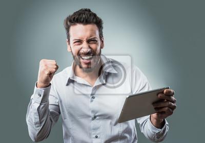 Wesoły uśmiechnięty młody człowiek z komputera typu tablet