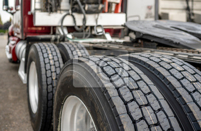 Naklejka Wheels with tires on axels of big rig semi truck standing on parking lot
