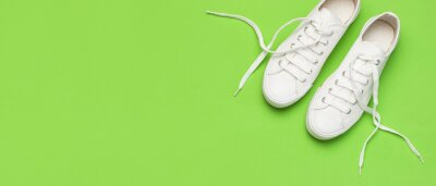 Naklejka White female fashion sneakers on green background. Flat lay top view copy space. Women's shoes. Stylish white sneakers. Fashion blog or magazine concept. Minimalistic shoe background, sport shoes