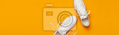 Naklejka White female fashion sneakers on yellow orange background. Flat lay top view copy space. Women's shoes. Stylish white sneakers. Fashion blog or magazine concept. Minimalistic shoe background, sport
