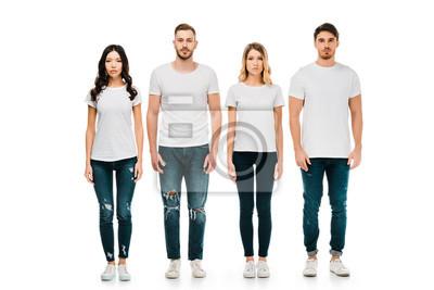 Naklejka widok pełnej długości poważnych młodych mężczyzn i kobiet w białych koszulkach i jeansowych spodniach stojących i patrząc na kamery na białym tle