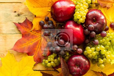 Widok z góry na czerwone soczyste dojrzałe jabłka z winogron i liści klonu jesienią na drewniane tła