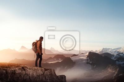 Naklejka Widok z tyłu człowieka stojącego na klifie przed zachodem słońca