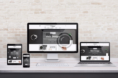 Naklejka Wiele urządzeń wyświetlających z nowoczesną witryną internetową o płaskiej konstrukcji. Drewniane biurko i wnętrze ceglanego muru.