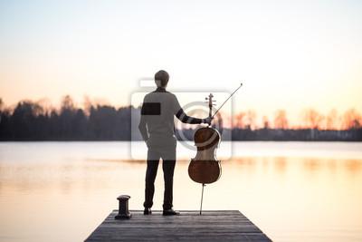 Naklejka Wiolonczelista wiolonczelista muzyk gra muzyka jako profesjonalny w lecie podczas zachodu słońca, bardzo relaksujący