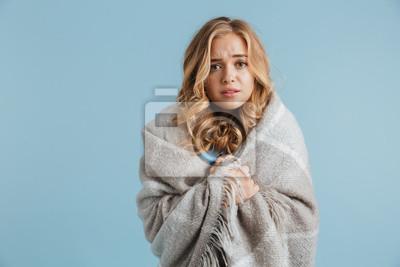 Naklejka Wizerunek niezadowolona kobieta 20s zawijająca w koc patrzeje kamerę, odizolowywająca nad błękitnym tłem