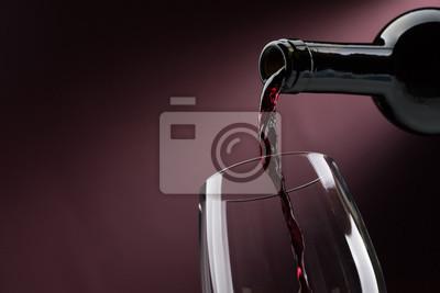 Wlewanie czerwonego wina do kieliszka do wina
