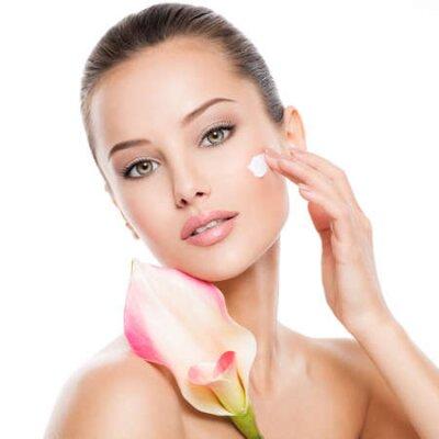 Naklejka Woman applying cosmetic  cream on a face. Fresh flower on the body