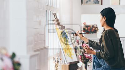 Naklejka Woman Artist Works on Abstract acrylic painting in the art studio.