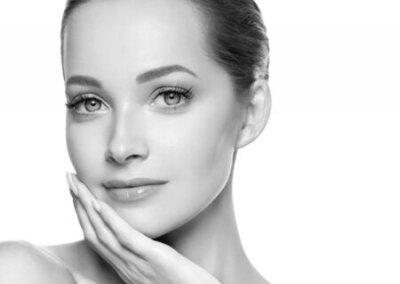 Naklejka Woman beauty face healthy skin natural makeup beautiful young model. Studio shot. Monochrome. Gray. Black and white.