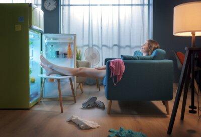 Naklejka Woman cooling herself in front of the open fridge