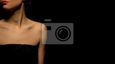Naklejka Woman in seductive black dress standing against black background, prostitution