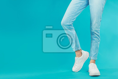 Naklejka Woman in stylish sport shoes on light blue background. Space for text
