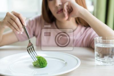 Naklejka Woman on dieting. Depressed teen looking at her empty plate dinner.