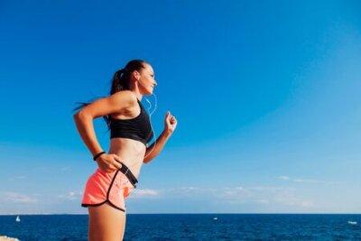 Naklejka woman on the run sports runs on the beach listening to music