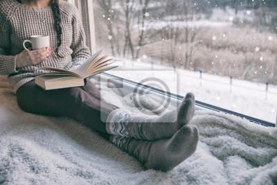 Naklejka Woman sitting by the window reading book drinking coffee. Winter snowing landscape outside