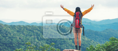 Naklejka Women hiker or traveler with backpack adventure feeling victorious facing on the mountain, outdoor for education nature on vacation. Travel and Lifestyle Concept
