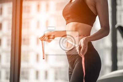 Naklejka women in fitness uniform And it is using the waist line in gym.