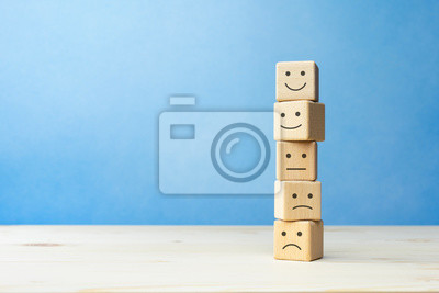 Naklejka Wooden blocks with the happy face smile face symbol symbol on the table, evaluation, Increase rating, Customer experience, satisfaction and best excellent services rating concept with copy space