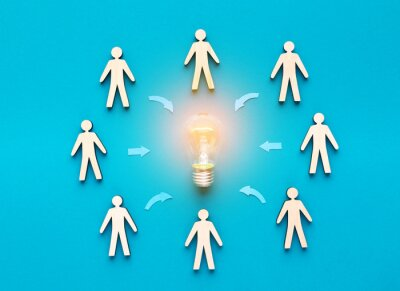 Naklejka Wooden cut out human figures around light bulb on blue