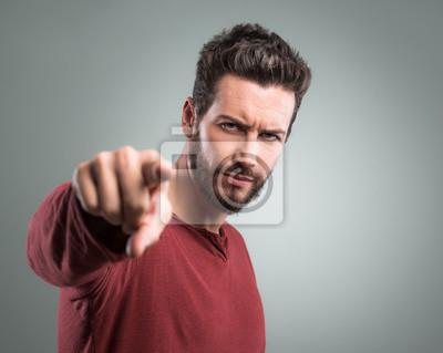 Wściekły młody człowiek wskazując na aparat fotograficzny