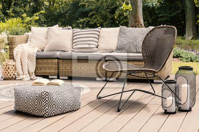 Naklejka Wzorzyste pufy i krzesło z rattanu na drewnianym patio z poduszkami na kanapie i lampionami. Prawdziwe zdjęcie