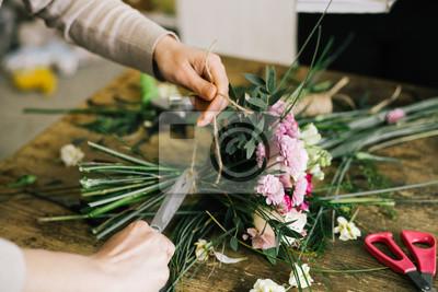 Naklejka Девушка флорист собирает красивый букет dziewczyna kwiatka sprawia, że piękny bukiet