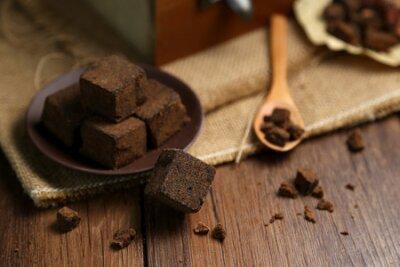 Naklejka Kawałki brązowego cukru w drewnianych pudełkach i talerzach