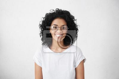 Naklejka Kryty portret pi? Knej brunetki m? Odych ciemnoskórych kobieta z shaggy fryzura u? Miechni? Te weso? Ami, wykazuj? C jej bia? E z? Bów do aparatu, podczas gdy czuje si? Szcz ?? liwy i beztroski na j