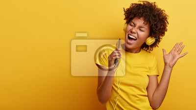 Naklejka Yeah, I am pleased. Joyful lovely dark skinned woman raises hand in dance move, likes great sound in new headphones, sings loudly, carries cellular, smiles broadly, wears yellow casual clothes