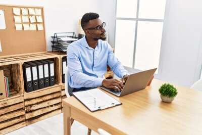 Naklejka Young african american man smiling confident working at office