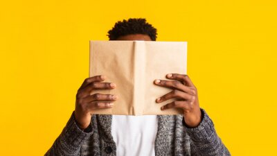 Naklejka Young african student pretended as if he was reading a book