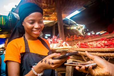 Naklejka young african woman selling tomatoes in a local african market receiving payment via mobile phone transfer