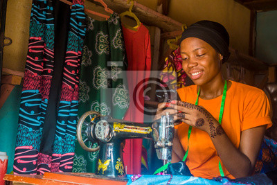 Naklejka young african woman who is a tailor smiling while using her mobile phone