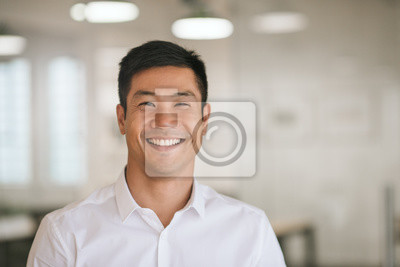 Naklejka Young Asian businessman standing in an office smiling confidently