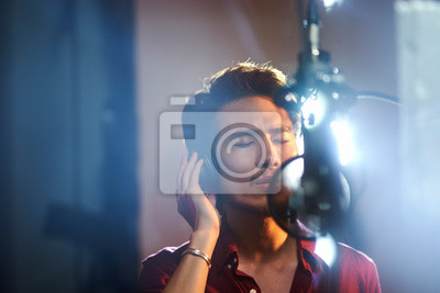 Naklejka young asian musician recording songs in studio