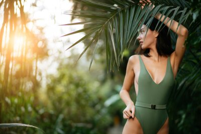 Naklejka young attractive charming model around green fresh plants, slim slender female with short dark hair, posing at camera wearing green beautiful swimsuit or bikini. people and nature