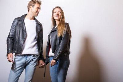 Naklejka Young beautiful couple in black leather jackets pose in studio.