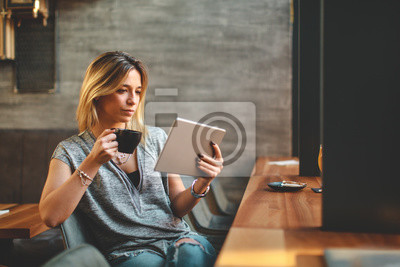 Naklejka Young beautiful woman relaxing in coffee shop reading electronic book via internet on digital tablet and drink coffee